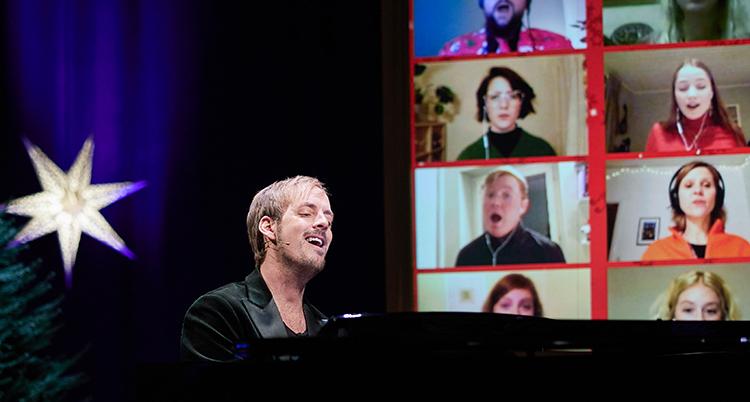 Han sitter vid ett piano. Bakom honom syns en stor skärm med folk som filmat sig själva hemma när de sjunger.
