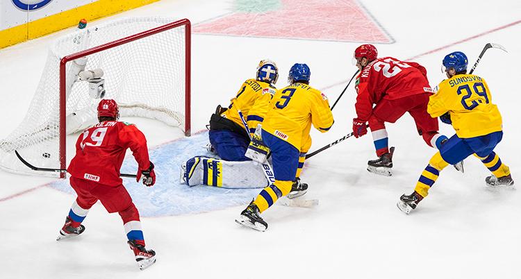 Ishockeyspelare i röda och gula tröjor framför målet. En spelare i rött har gjort mål.