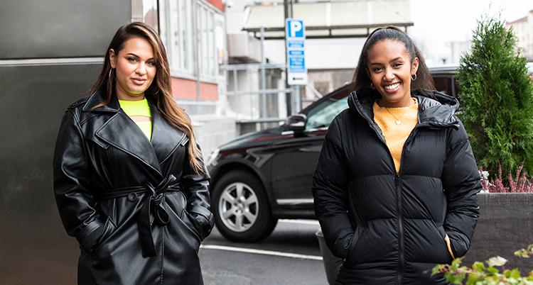 Två kvinnor i svarta ytterplagg står utomhus, på en parkeringsplats, intill ett hus