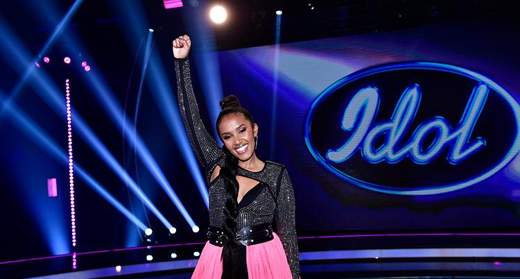 En kvinna med svart topp och rosa kjol sträcker höger knytnäve mot luften. I bakgrunden syns loggan Idol i blått.