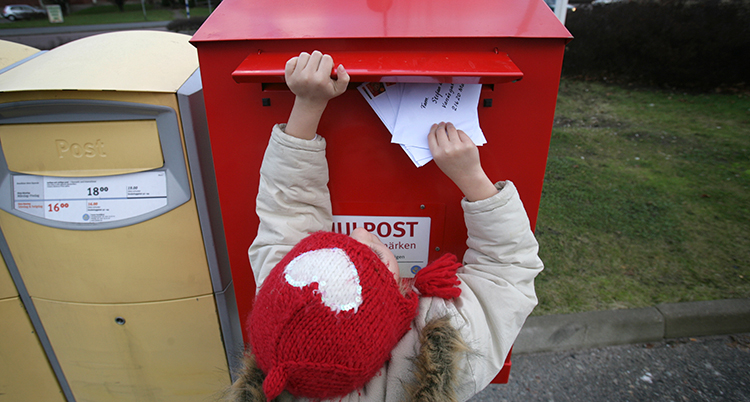 Ett barn med röd mössa stoppar ner ett brev i en röd brevlåda.