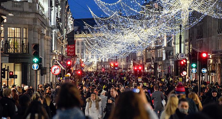Massor av människor med munskydd går på en gata.