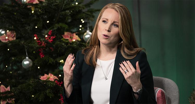 Annia Lööf pratar och lyfter båda händerna i en gest. Bakom henne står en julgran.