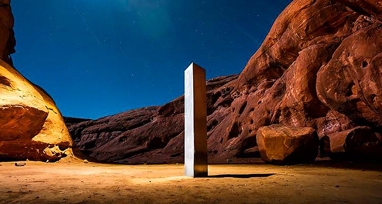 Det är kväll. En ensam pelare står på en sandig mark. Bakom den är berg. Det snett ljus lyser upp pelaren så den ser fysisk ut.
