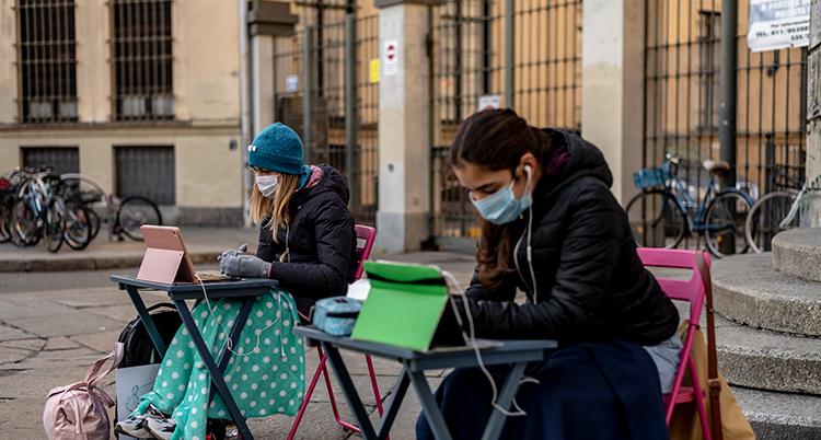 De sitter vid två bord utomhus framför en skola. De har munskydd på sig.