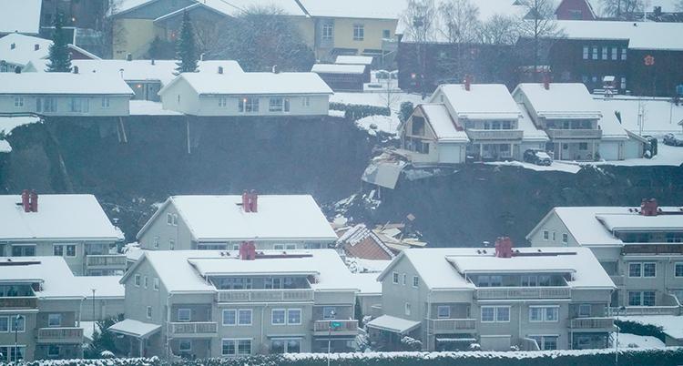 En suddig bild som visar ett område med flera villor. Mitt i bilden är det svart. Det är ett stort långt hål. Några hus har rasat ner.