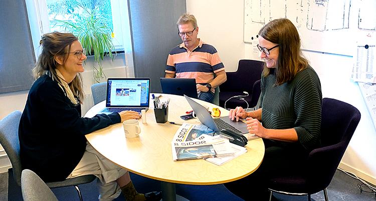 Tre personer sitter runt ett bord.