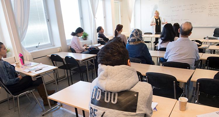 Elever sitter vid skolbänkar i ett klassrum