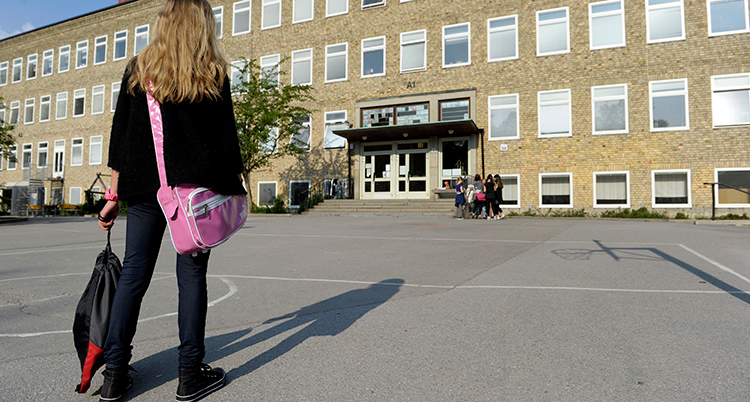 En flicka med en rosa skolväska över axeln och gympapåse i handen går över en asfalterad skolgård mot en skola i gult tegel