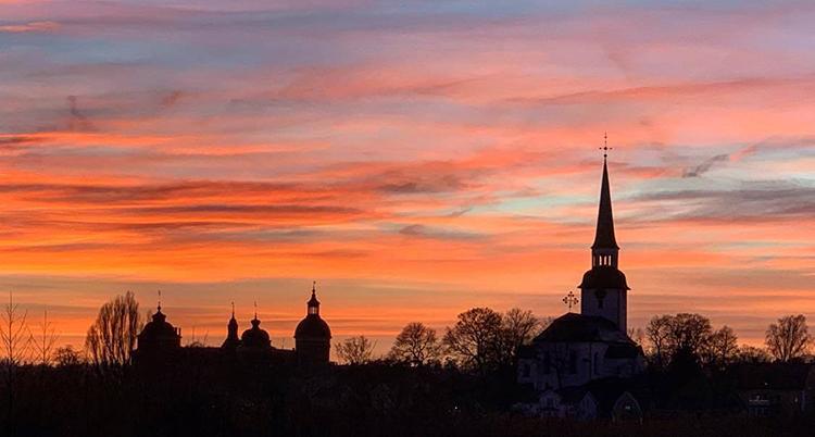 Siluetterna av ett slott och en kyrka och träds syns i svart mot en rosaröd himmel.