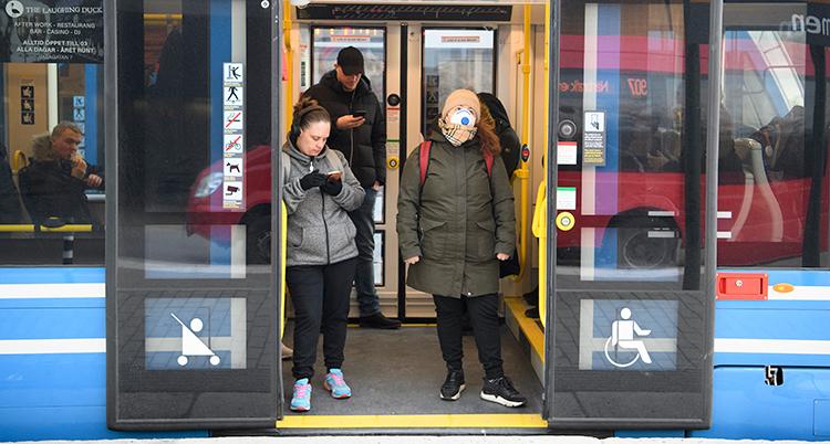 Två personer har klivit på en buss. Dörrarna har inte stängt sig ännu. En av personerna har munskydd.