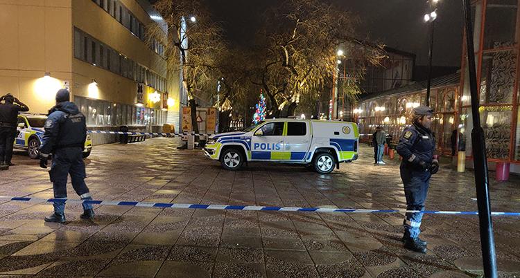 Poliser och en polisbil på en mörk gata.