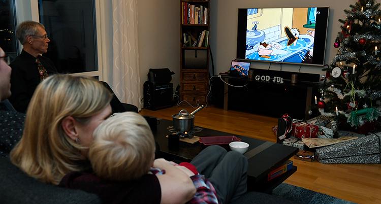 Huvudet på en kvinna och ett litet barn syns i en soffa. De tittar på en tv med Kalle Anka som badar i rutan.