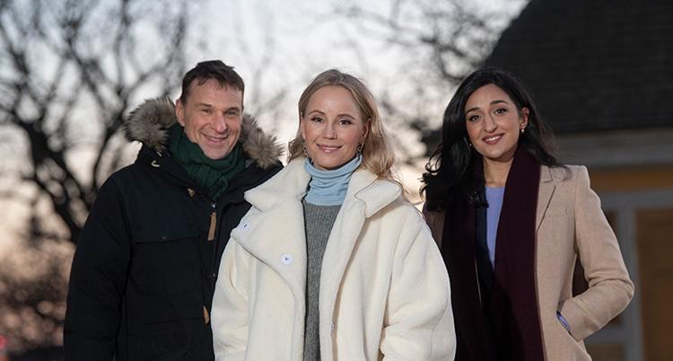 Tre personer tittar in i kameran, en man och två kvinnor. De står utomhus på Skansen.