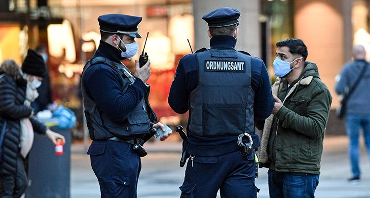 En man står och pratar med två vakter. Alla har munskydd.