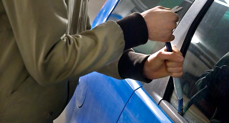 En person försöker bryta sig in i en bil med en kofot. Det är en blå bil. Bilden är arrangerad. Det är inte på riktigt.