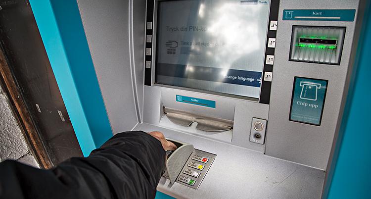 En person tar ut pengar från en bankomat. Vi ser bara armen på personen. Bankomaten har en skärm och olika knappar.