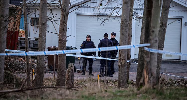 Tre poliser står utomhus. De står vid ett vitt garage. Poliserna har satt upp vita och blå band mellan träd.