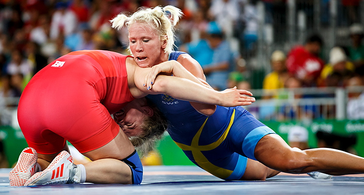 En match i brottning. Två kvinnor brottas. Jenny Fransson har ljust hår och blå dräkt. Kvinnan hon brottas mot har röd dräkt.