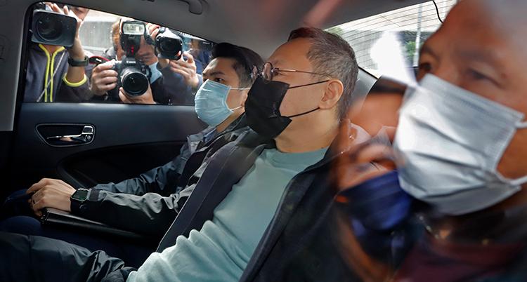 en bil kör iväg med tre män i munskydd i baksätet. Han i mitten är den gripna.