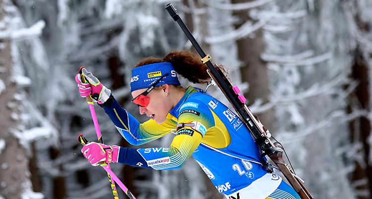 Hanna Öberg åker skidor. Hon har ett gevär på ryggen. Hon har en dräkt som är blå och gul. Och hon har glasögon med röda glas.