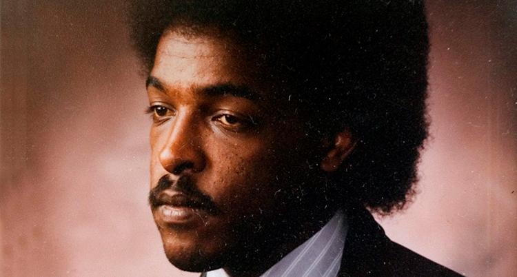Ett gammalt porträtt på Dawit Isaak. Han ser allvarlig ut. Han tittar inte in i kameran. Han har stort svart hår och mustasch. Han har kavaj och skjorta.