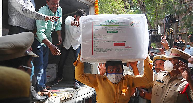 Bilden är tagen i Indien. Människor lastar av lådor från en lastbil. En man har tagit en stor låda som han bär på sitt huvud. Poliser vaktar vid lastbilen.
