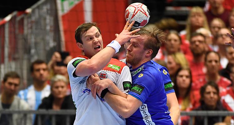 Bilden är från en match i handboll. Två spelare kämpar om bollen. En spelare har en vit tröja. Den andra har en blå tröja.