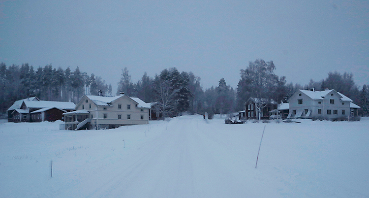 Bilden är tagen i en by på landet. Det är mycket snö på marken. Vi ser några hus. Det är helt mörkt i fönstren.