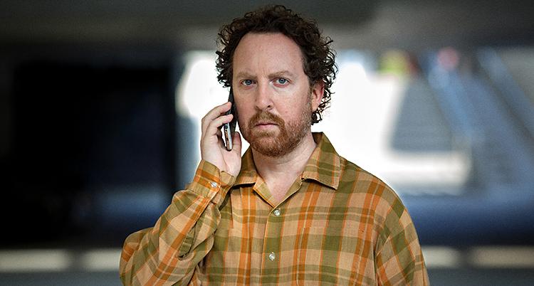Uje står och pratar i en telefon. Han har lockigt hår som är lite rött. Han har ett kort skägg. Och han har en rutig skjorta som är brun, röd och grön.