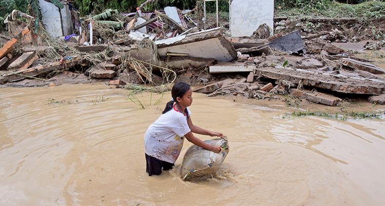 En flicka håller en säck på en översvämmad plats.