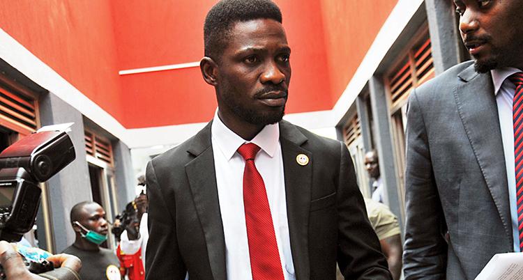 En bild på politikern Bobi Wine. Han har en mörk kostym, vit skjorta och en röd slips. Journalister vill prata med honom.