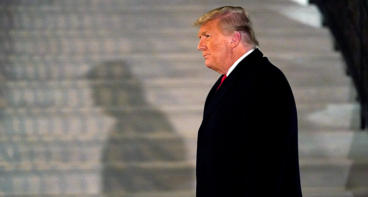 Donald Trump går utanför Vita huset. Vi ser honom i profil. Han har en svart rock på sig.