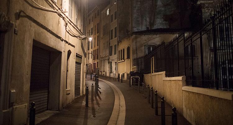 Bilden är tagen på kvällen. Vi ser en gata med hus. Några gatlampor lyser. Inga människor är där.
