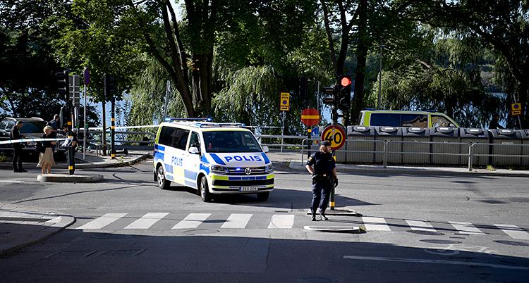 En gata i Stockholm. Poliser har spärrat av med vita och blå band. Vi ser en polisbil och poliser som går på gatan.