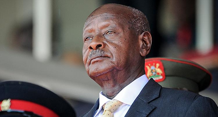 En närbild på presidenten i Uganda som heter Yoweri Museveni. Han är en äldre man med snaggat huvud och en mustasch. Han har kostym. Bredvid honom står några militärer.