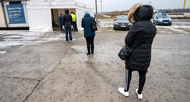 Människor står i en kö utomhus. De har stort avstånd mellan varandra. De köar till ett vitt tält där de ska få testa sig.