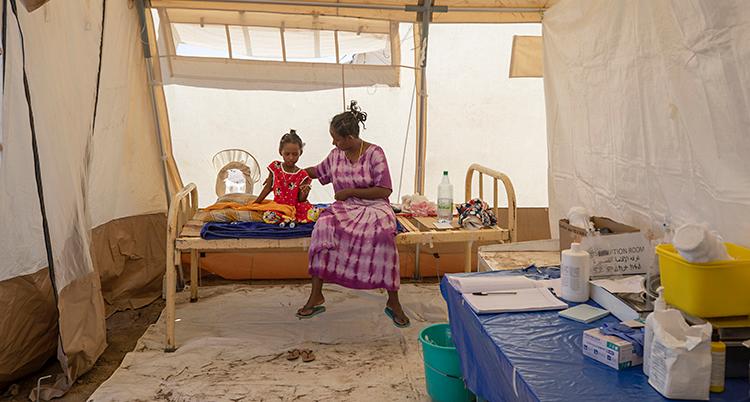 Bilden är från ett läger för flyktingar. Två personer sitter på en säng i ett vitt tält. Det är en kvinna och ett barn.
