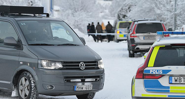 Vi ser en gata. Det är snö på gatan. Flera polisbilar står på gatan. Och längre bort står några poliser.
