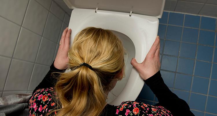 En kvinna lutar sig över en toalett. Hon mår dåligt. Vi ser henne bakifrån. Hon har blont hår och en blommig tröja.