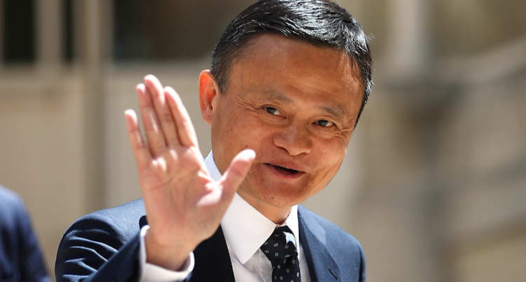 En bild på Jack Ma. Bilden är tagen utomhus. Han ler och vinkar mot kameran. Han har kort svart hår och kostym.