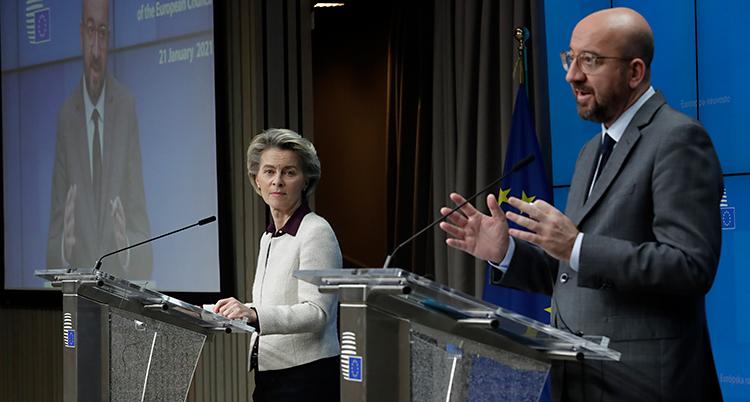 Två personer står i en sal. De står framför varsin talarstol där det finns en mikrofon. En kvinna står till vänster. En man står till höger. Han pratar i mikrofonen.