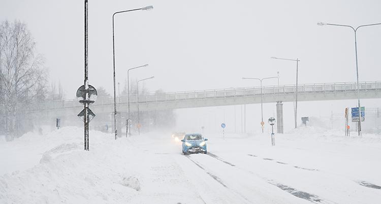 Vi ser en bilväg i staden Umeå. Några bilar kör på vägen. Det är snöigt på vägen och mycket snö bredvid vägen.