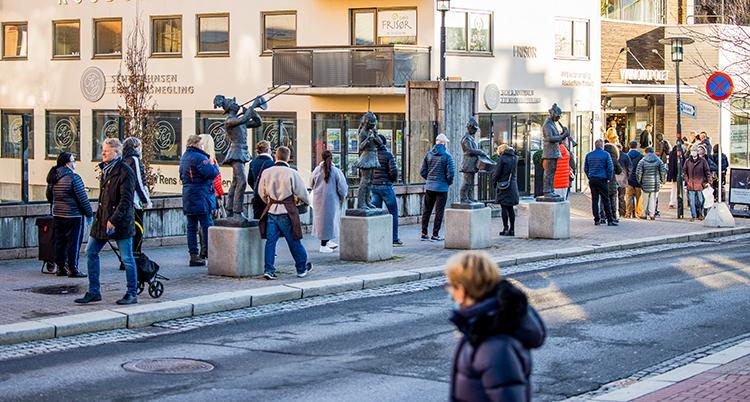 En lång kö på en trottoar till en butik.