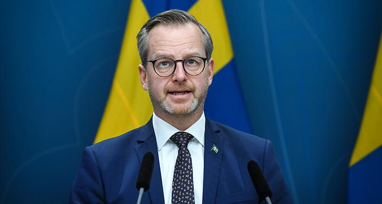 Mikael Damberg framför en svensk flagga.