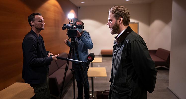 En man med skägg blir intervjuad. Reportern har sin mikrofon på en pinne. En person med kamera står och filmar intervjun.