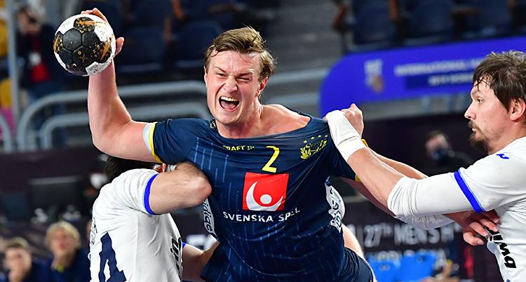 Det är en match i handboll. Den svenska spelaren Jonathan Carlsbogård håller i bollen. Han har en blå tröja. En rysk spelare sliter honom i tröjan.