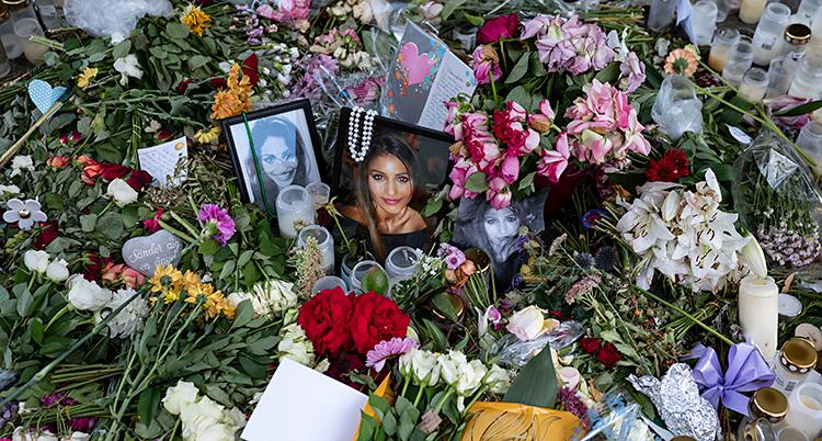 Det ligger massor av blommor på gatan. Även foton på kvinnan som blev mördad.