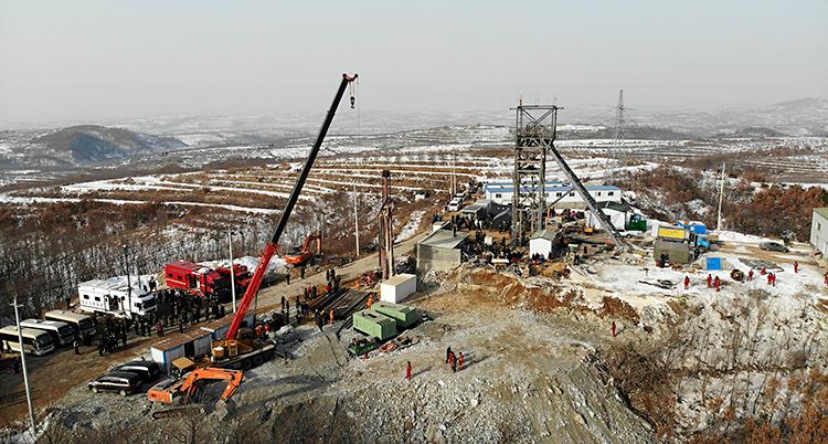 Bilden är tagen högt uppifrån. Nere på marken syns en massa människor och stora maskiner.