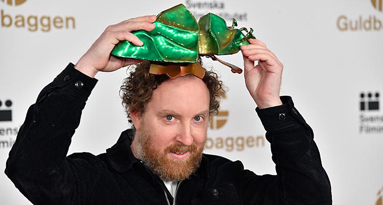 Uje är glad. Han lyfter upp en guldbagge ovanför sitt huvud.